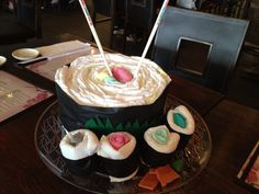 "Sushi diaper ""cake"" for baby shower at Japanese restaurant. Diapers, washcloths, socks, black plastic table cloth for seaweed, play- doh for ginger and wasabi."