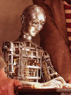 Made by a crew at Dick George, including Bill Thomas:  http://www.heyuguys.co.uk/2011/12/05/martin-scorseses-hugo-making-the-automaton-fantastic-behind-the-scenes-video/  It actually draws too!