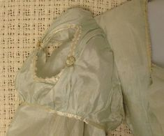 "Andrew H. Green Estate and Antiques Auction - Worcester, Massachusetts - U.S.A.  Lot 73. Regency Period China Silk Gown Circa 1805 Palest blue China silk gown. Lined sleeves with diamond cut out shoulder puffs trimmed in ivory ""pinked"" satin ribbon. Back closures are ivory silk corded loops that hook on fine silk thread wrapped buttons. Condition: Fabric is whole without rips or tears. Staining on front of gown and some light fading. Owner attribution based on date/style to Lydia Pinkham…"