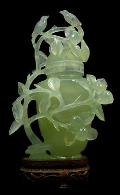 A Chinese openwork carved serpentine jade covered vase depicting birds perched on branches with flowers.