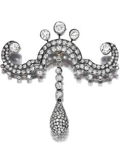 A mid Victorian diamond scroll brooch, French, circa 1860. designed as an old European-cut diamond scroll, suspending a pavé-set diamond drop; with French assay mark, mounted in silver-topped 18k gold.