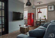 Сдержанные цвета зоны гостиной-столовой разбавлены красными акцентами светильника Toscot и холодильника Smeg. Акриловый столик сделан на заказ в Беларуси, а декоративная вязанка сена напоминает о луговых альпийских ароматах.