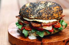 greens. oven-dried tomatoes. roasted chicken. and. an over-medium egg. on a poppy seed. bagel. with buttermilk. dressing.