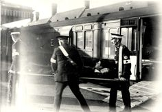 St. John's Ambulance men helping to unload cot cases at Boscombe train station. Credited to Bournemouth Library.