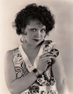 """SUNBURN TATOO [sic] - - Clara Bow, Paramount's dynamic redhead, prepares herself for the seasonal pastime of sunburning a design upon her shoulder. Cutout figures of any pattern may be used. Just stick them on that part of the body you wish to decorate and let the sun do the rest."""