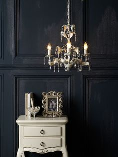 A cream chandelier could work anywhere, but I like the idea of one by a matching entryway table like this