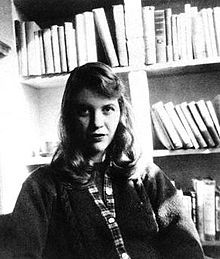 Sylvia Plath Academic, Author, Editor, Poet (1932–1963) A black-and-white photo of a woman with shoulder-length hair. She is seated facing the camera, wearing a sweater, with bookshelves behind her.