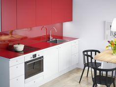 FAKTUM kitchen with APPLÅD white doors/drawers, RUBRIK APPLÅD red doors and NUMERÄR double-sided worktop