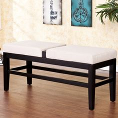 Add extra seating to your living space with this black contemporary bench. Featuring an open design, this wooden bench is set with two cream microfiber cushions. The convenient hook-and-loop fasteners keep your cushions securely attached.