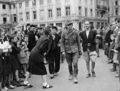 The newly liberated French citizens mock and spit on a German POW as he's escorted by members of the French resistance, 1944