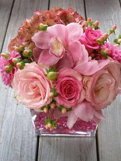 """Designed specifically for a wedding Reception, I unfortunately do not think that this photgraph does the piece justice.  Featuring hydrangea, cymbidium orchids, Esperance and Ravel roses -cut down from the large head long-stems, dahlia and hypericum, the all-around design was presented in a large, clear, rectangular vase filled with pink """"gemstones"""".  A gorgeous piece but one that did not out-shine the charming, gracious and wonderful couple getting married."""