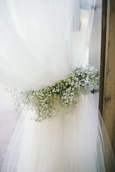 Curtains tied back with a garland of baby's breath