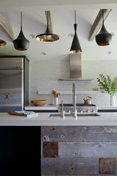 Stunning kitchen with Tom Dixon Beat Lights over re-claimed wood kitchen island. Salvaged wood kitchen island with white countertops and sink. Kitchen features rustic exposed wood beams and steel kitchen hood and white floating shelf over stainless steel gas range.