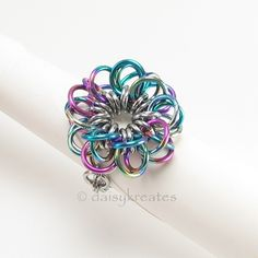 Forget-Me-Not Flower Cocktail Finger Ring:   Woven in a modified version of Lorenz's Forget-Me-Not chainmaille pattern with custom anodized niobium and stainless steel jump rings, the ring features a flower design with soft petals and subtle movements reminiscent of the flower of its namesake.