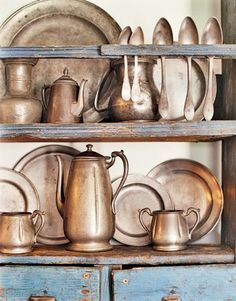 a lovely collection of pewter, displayed against chalky blue wood.
