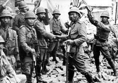 Stern faced Japanese officer and marines pause and wave the flag of the Rising Sun in the rubble of a conquered Chinese town