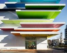 """An offset volume of rainbow-like layers for facade of the Sugamo Shinkin Bank in Shimura, Japan - Stacked slabs in twelve saturated colors dominate the exterior facade and contrast the stark white panels that enclose the building. The colors gently transition until they disappear into the sky - """"Sugamo Shinkin Bank"""" by Emmanuelle Moureaux Architecture + Design, Tokyo, Japan"""