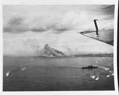 """Iwo Jima under bombardment as the initial landing craft waves retract on D-Day, 19 February 1945. Note smoke rising from Mount Suribachi, in center. A Cleveland-class light cruiser is in the lower right."" (NHHC: 80-G-412489)"