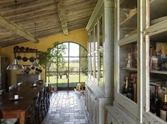 In Tuscany a farmhouse was sensitively restored by designer Andrea Gobbi and its owners. In the fabulous kitchen, the large century-old dressers came from a local school. Around the table are tavern chairs from the 19th century. From At Home in Italy | Quintessence.