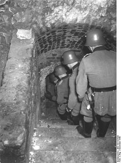 """Police operation in the Lublin Ghetto, December 1940. The police troops descend into one of the secret vaults below the ghetto in search of hidden assets of the Jewish community. This is still the beginning and the Germans are fresh and polished. Note the ceremonial dagger carried by the officer in the foreground. Ceremonial weapons were rarely carried during """"Aktionen"""" (ops against the Jews and other 'undesirables')."""