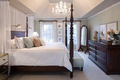 Tray ceilings frame a crystal chandelier having over the dark wood four-poster bed. Polished nickel, task-style sconces serve as reading lights on each side of the bed.