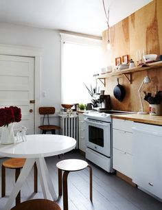 Love love love the random bits of wood and the contrast of the bright white. And of course, the cast iron pan. It's a thoughtfully simple kitchen that didn't cost a zillion dollars.