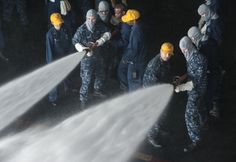 ARABIAN GULF (Jan. 17, 2014) Sailors man a hose during a general quarters drill in the hangar bay of the aircraft carrier USS Harry S. Truman (CVN 75). Harry S. Truman, flagship for the Harry S. Truman Carrier Strike Group, is deployed to the U.S. 5th Fleet area of responsibility conducting maritime security operations, supporting theater security cooperation efforts and supporting Operation Enduring Freedom. (U.S. Navy photo by Mass Communication Specialist 3rd Class Karl Anderson/Released)