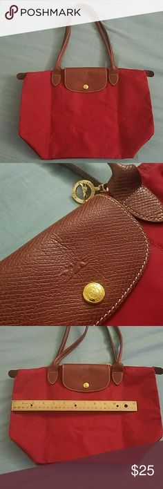 Medium zippered tote bag Not sure if this is real Longchamp but has the logos.   Pictures show it is bright red but it is actually dark red.   Great condition! Used a couple times. Little to no signs of ware.   Folds up for easy storage.   One inner pocket. Bags