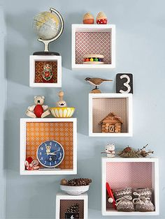 Line mounted boxes with a mix and match of wallpaper to create a quirky cool storage design in a kid's room.