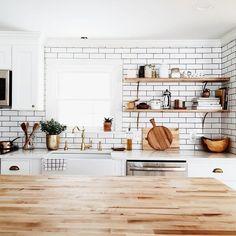 white subway tile farm sink brass open shelving kitchen.