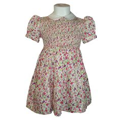 """Emily (Cream & Pink) - Traditional smocked dress. Short puff sleeves and white """"Peter Pan"""" collar piped in matching floral fabric. Button up back with tie back belt in same floral fabric. Available in sizes 6 months - 8 years."""