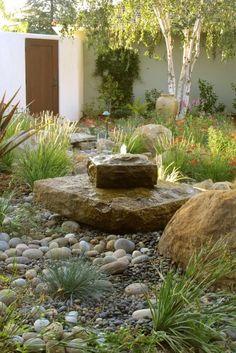mediterranean landscape by Margie Grace - Grace Design Associates - charming, stone water feature.