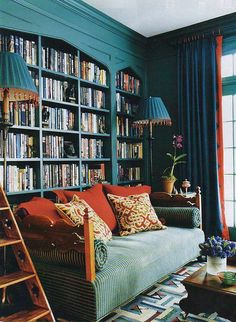 teal library with built-in bookcases -- love the color with the splashes of orange