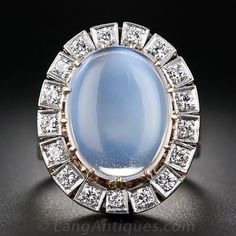 Large Vintage Moonstone and Diamond Ring, This sensational and sizable moonstone and diamond ring hails from the 1930s-1940s and was conceived with late-nineteenth century Victorian style in mind. The glowing 'blue flash' gemstone is held aloft by thirteen lightly sculpted coronet prongs and is encircled by seventeen sparkling European-cut diamonds set in square white gold settings. The engraved bowl-shape undergallery and ring shank (along with the prongs) are in contrasting yellow gold.