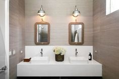 Cottage bathroom features grasscloth clad walls framing a pair of rope mirrors illuminated by vintage barn sconces over floating washstand fitted with his and her vessel sinks paired with modern faucets.