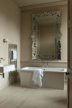 reforma baño con bañera exenta, lavabo sin pedestal, bañera exenta, suelo parquet pintado blanco, radiador toallero y gran espejo. www.presupuestON.com