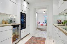 biała kuchnia skandynawska z drewnianymi blatami w naturalnym kolorze