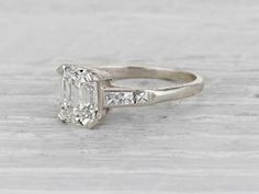 Vintage Art Deco engagement ring made in platinum and centered with a GIA certified 1.91 carat I color VS2 clarity emerald cut diamond. Accented with six french cut diamonds. Circa 1925. French cuts are a lovely accent to the center stone. This ring pairs well with a wedding band, a beautiful example of the period. Diamond and gold mining has caused devastation in areas such as Africa, wreaking havoc on delicate ecosystems and communities. Choosing to go vintage, you are eliminating the need…