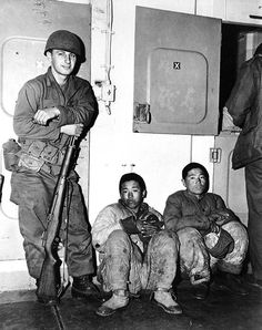US Marines guarding 2 North Korean prisoners aboard a transport ship which was probably traveling from Hungnam to Pusan, Korea, late Dec 1950; note M1 Garand rifle with safety at 'off' position.