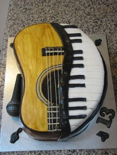 Half guitar half keyboard.   This is not an original idea but I did my own take on it. The microphone is all chocolate.  The rest is chocolate mud cake decorated with fondant and modelling chocolate.