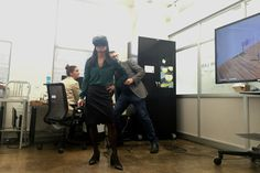 Maria Torres-Springer tries out a virtual-reality headset at a press conference announcing plans for a virtual-reality