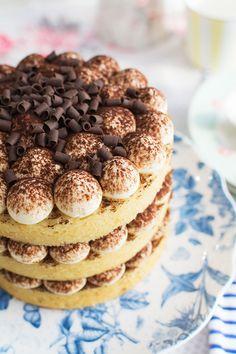 Nude Cake de tiramisú sobre stand para tartas El tiramisú es un clásico de la repostería italiana, tiene un sabor intenso y único, fácilmente reconocible por todos los amantes del cacao y el café, entrelos cuales me incluyo. Por eso, en el vídeo de esta semana, os muestro cómo hacer una nude cake detiramisú. Es una forma perfecta de llevar el sabor de este delicioso postre a una tarta, para celebrar eventos muy especiales. Primero hacemos un bizcocho de vainilla que nos va a recordar a…