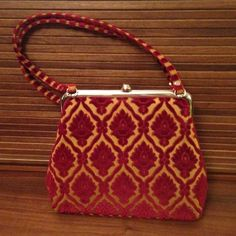 """M. Antonia Red and Gold Brocade Handbag with Clasp M. Antonia vintage-look handbag with red and gold velvet brocade fabric. Contrasting red and gold striped straps and bottom details are stunning. Gold interior with pocket and silver metal clasp closure, details and feet on the 4.5"""" base. Bag measures 10""""h x 11""""w. Gorgeous bag!! Like New. M. Andonia Bags"""