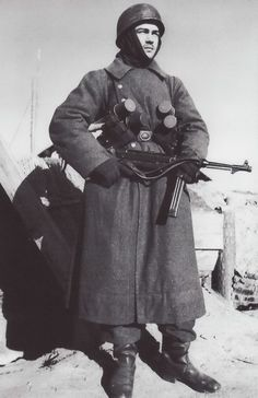 A German paratrooper is standing guard in front of an improvised shelter. Apart from the MP40, he is carrying as many as four stick grenades, undoubtedly at special request of the photographer. Note the Luftwaffe belt buckle and the rubber muzzle cap on the MP40. Due to heavy losses during the conquest of Crete in the spring of 1941, the German paratroopers were afterwards mainly used as ground troops. Pin by Paolo Marzioli
