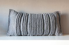 Grey knitted pillow.