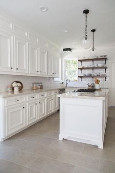 Beautiful kitchen features white cabinets paired with Taj Mahal Quartzite countertops and a white subway tiled backsplash.