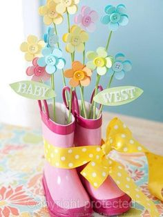 Baby shower centerpiece - paper flowers on painted bamboo skewers inside a pair of child's rain boots - sweet! Description from pinterest.com. I searched for this on bing.com/images