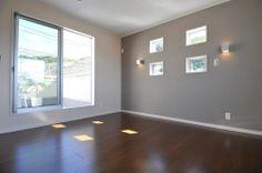 ウォールナットの床とライトグレーのアクセント壁