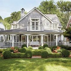Cedar shakes give this house a Nantucket feel. Love the wrap around porch and the charming second story balcony.