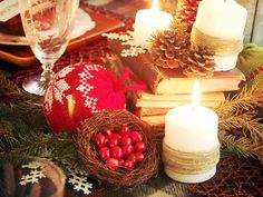 """Layer Upon Layer: Fluffy white snowflakes, knit """"sweater"""" ornaments, twine-wrapped candles, fresh greens, pinecones and a stack of old books bring visual and textural interest to this centerpiece. Be careful where candles are positioned in relation to fresh greenery, and never leave candles unattended. christmas table decorations, christmas tables, shades of red, christmas decorations, red christma, christmas decorating ideas, christmas candles, rustic christmas, old books"""